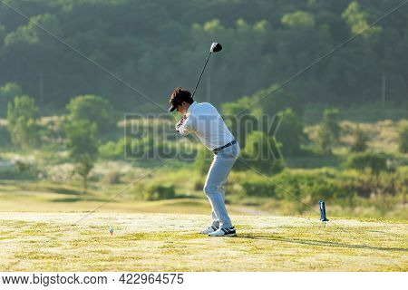 Golfer Sport Course Golf Ball Fairway. People Lifestyle Man Playing Game And Swing Golf Tee Off On