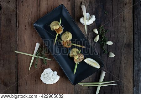 Top view of a skewer of seared hokkaido scallops with lemongrass flavouring served with curry cauliflower sauce isolated on wooden table