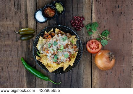 Plate of delicious corn chips nachos in cheddar cheese with beans, tomato, green chili, black olives, cilantro served with guacamole, sour cream and tomato salsa dip on the side isolated on the wooden