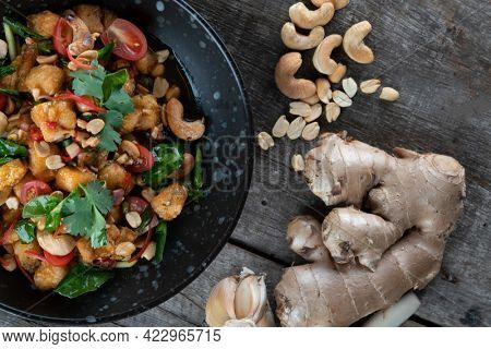 Gai Pad Med Mamuang or Thai Cashew Chicken in black bowl on wooden rustic table