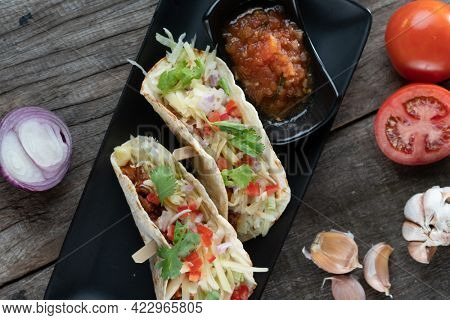 Slow cooked short ribs on tortillas with a spring onion tomato salsa isolated on wooden table