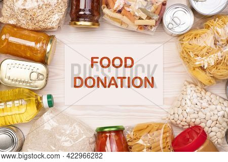 Food donations such as pasta, rice, oil, peanut butter, canned food, jam and other on white wooden table, top view with copy space