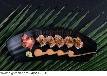 Top view of Sushi Roll - Maki Sushi made of tuna, avocado, mayonnaise and ebiko sushi isolated on black table with tropical leaves