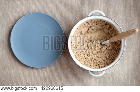 Oatmeal In A Saucepan With Empty Plate. Oatmeal Breakfast In The Morning