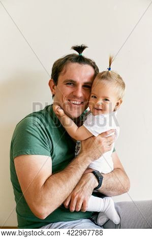 Smiling Dad And Little Girl With Ponytails Sit Hugging