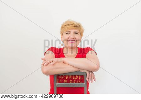 Pretty Middle-aged Woman. Short Blonde Hair. Medium Build. Dressed In A Red T-shirt, Blue Jeans And