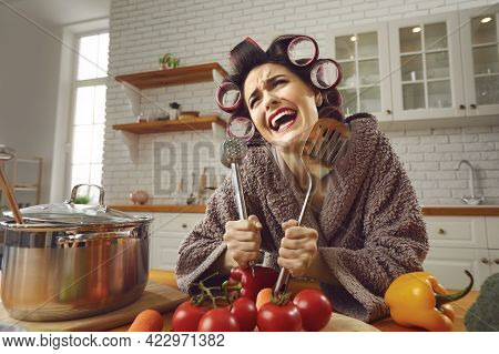 Funny Crazy Cheerful Woman Standing In Kitchen And Holding Kitchenware