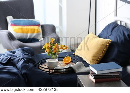 Cup Of Coffee, Orange And Flowers On Bed With Fresh Linens Indoors