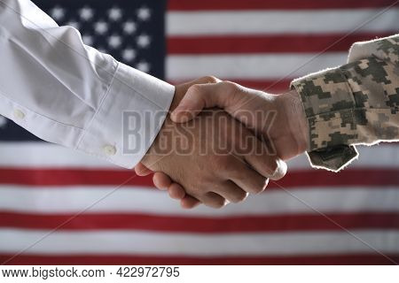 Soldier And Businessman Shaking Hands Against Flag Of Usa, Closeup