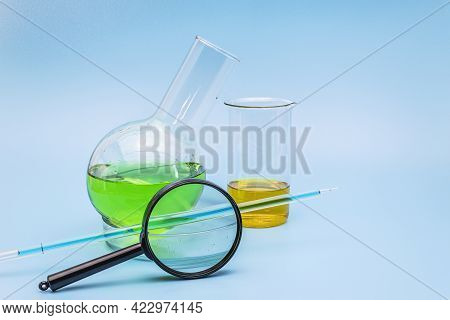 Glass Laboratory Flask And Beaker In A Cup With A Green And Yellow Solution With A Magnifying Glass