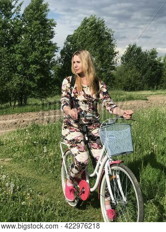 A Girl In A Tracksuit Posing On A Bicycle. On The Lawn In The Park.