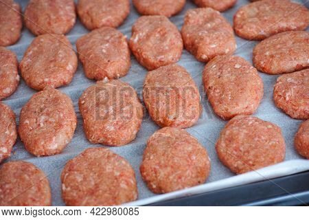Raw Beef Patties On A Baking Tray. Close Up.