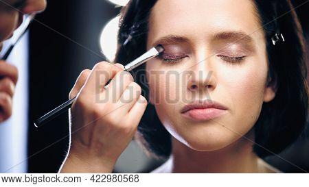Blurred Makeup Artist Applying Eye Shadow With Cosmetic Brush On Eyelids Of Model.