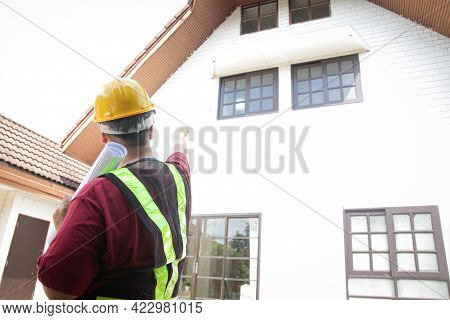 A Male Engineer Inspects The House To Deliver It To The Customer. Standing In Front Of The House, Po