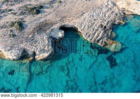 Greece, Cyclades. Aerial Drone View Of Steep Rocky Coastline Over Green Emerand Sea Water