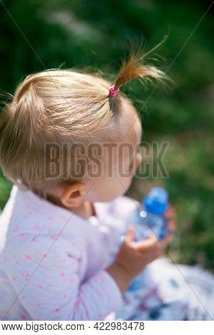 Little Girl With A Ponytail Holds A Plastic Bottle In Her Hands. Top View