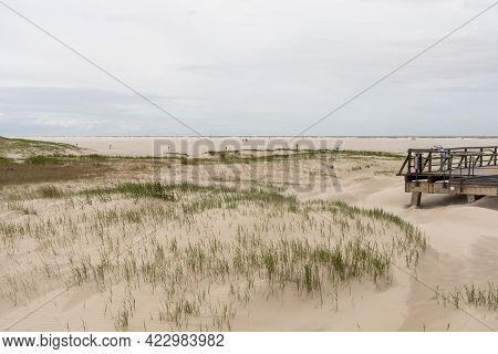 View Of An Expansive Sandy Beach On The German Wadden Sea Coast With A Wooden Boardwalk