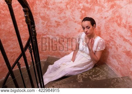 Beautiful young woman in authentic regency gown posing on spiral antique staircase