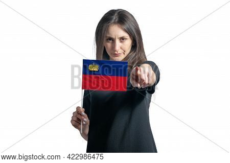 Happy Young White Woman Holding Flag Of Liechtenstein And Points Forward In Front Of Him Isolated On