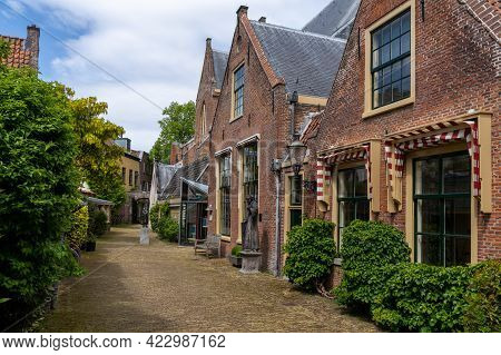 Haarlem, Netherlands - 21 May, 2021: Picturesque Neighborhood Street With Red Brick Buildings In The