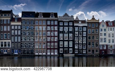 Amsterdam, Netherlands - 19 May, 2021: View Of The Iconic Houses On The Waterfront At The Damrak In