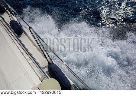 Part Of The Hull Of The Pleasure Yacht With Fenders Against The Foaming Sea At Full Speed.