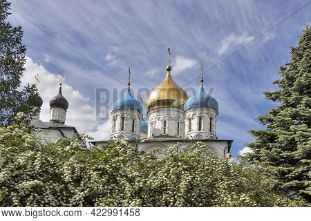 Moscow, Russia - May, 2020, The Domes Of The Novospassky Monastery Against The A Blooming Spiraea. N