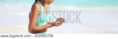 Fitness online app fit active girl using mobile phone for heatlh and exercise tracking progress on tech device. Panoramic banner of athlete woman monitoring her sport.