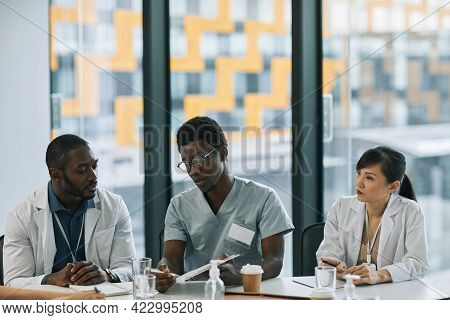 Multi-ethnic Group Of Doctors Discussing Case While Sitting At Meeting Table During Medical Council,
