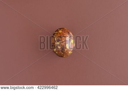 One Egg, Painted In Brown Colors, On Brown Background. Minimalism Concept. Unusual Pattern On Surfac