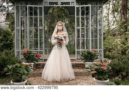 Full Length View Of Elegant Bride In Safety Mask Holding Wedding Bouquet Near Alcove In Park