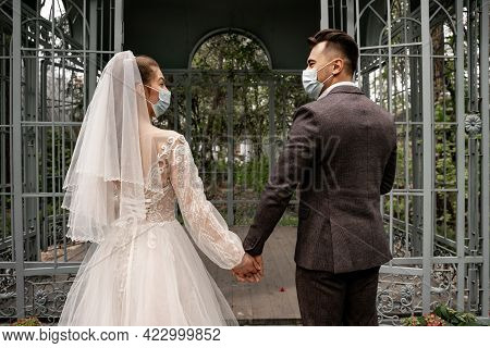 Back View Of Bride And Groom In Medical Masks Holding Hands Near Alcove In Park