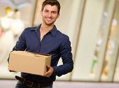 Young Man Holding Cardboxes, Indoors poster