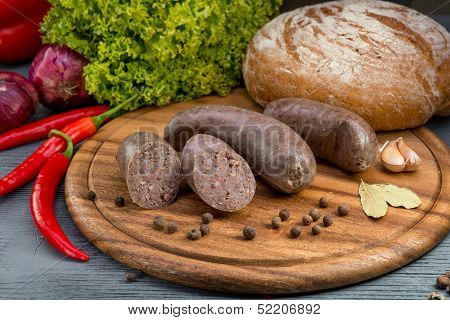 boiled sausages with vegatables and spices on grey wooden background poster