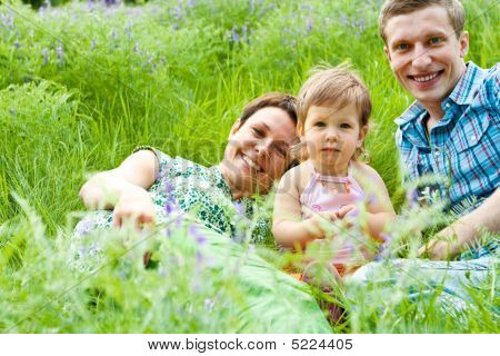 Parents And Their Daughter In Grass