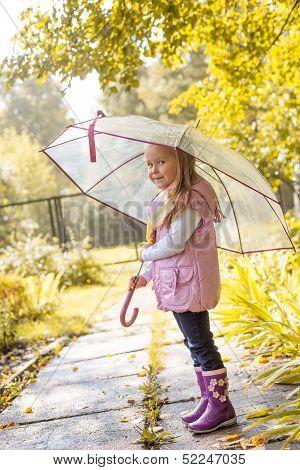 Slyly smiling girl posing under umbrella in park