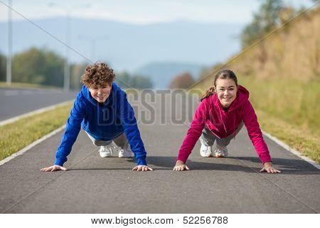 Teenage girl and boy doing push-ups