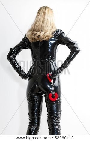 standing woman wearing extravagant clothes with handcuffs