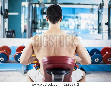 Back view of a stong man ready to lifting weights in the gym