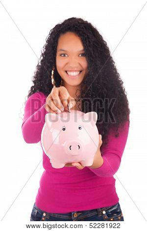 Young African American Woman Putting Coin In Piggy Bank