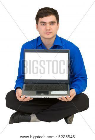 Kerl sitzt auf dem Stockwerk mit dem laptop