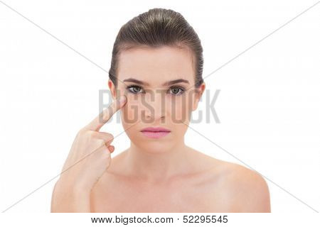 Serious natural brown haired model touching her cheekbone on white background