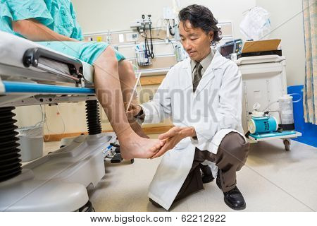 Full length of neurologist examining patient's tendon