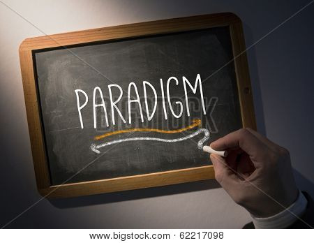Hand writing the word paradigm on black chalkboard