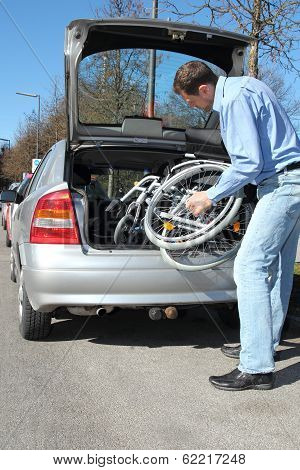 Man Packing A Wheelchair In A Car's Trunk