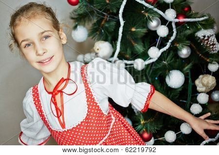 Smiling little girl dressed in white blouse and red pinafore dress with white polka dots stands against decorated christmas tree