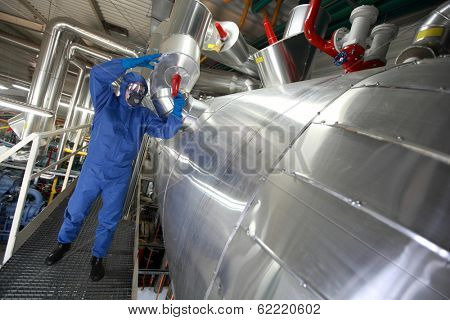 Technician in blue protective  uniform checking technological system