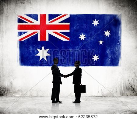 Two Businessmen Shaking Hands With Flag of Australia