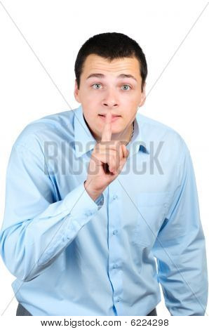 Businessman with his finger on his lips isolated on white