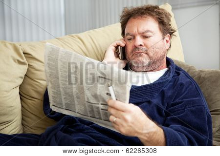 Unemployed man at home on the couch looking at the classified ads in the newspaper.